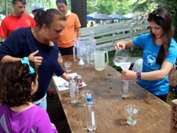 VIMS Ph.D. student Jessie Turner (R) helps guests build a Cartesian diver to learn about bouyancy.