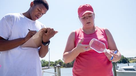 VIMS assistant professor Emily Rivest works with a local student to study experimental oysters deployed in the Rappahannock River as part of her Citizen Scientist Initiative. © Dominion Energy.