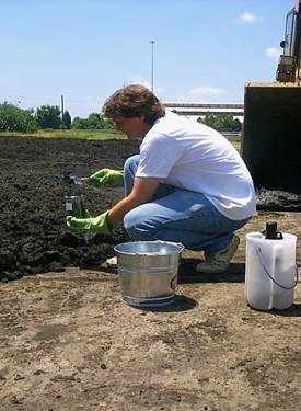 Professor Rob Hale takes a soil sample to help in his study of biosolids.