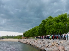 Invited guests and passersby applaud the christening from the shelter of the Yorktown shore as a storm front moves by. © D. Malmquist/VIMS.