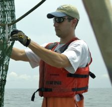 VIMS Ph.D. student Andre Buchheister checks out a trawl net during a ChesMMAP cruise to Chesapeake Bay.