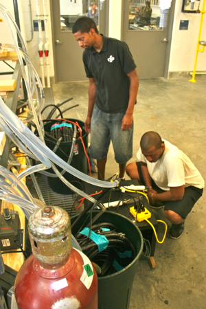 From L: Malik Breland and Cedrick Shamley Jr., of Hampton University prepare water lines for their study of the temperature preferences of Atlantic croaker. The pair are working with HU faculty member and VIMS alum Andrij Horodysky.