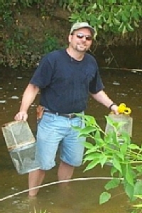 Mark LaGuardia collects samples from a freshwater stream for analysis of flame retardants.